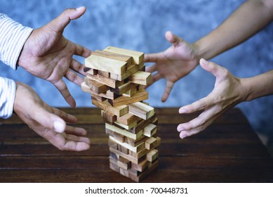 Hand of business man stopping falling wood blocks on table.concept  taking responsibility and risk.