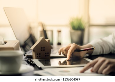 Hand of Business people calculating interest, taxes and profits to invest in real estate and home buying