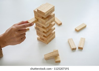 Hand of business people planning, risk and strategy in business.Businessman gambling placing wooden block on a tower.