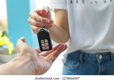 Hand of business woman gives the car key.