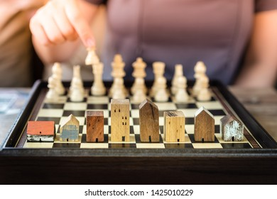Hand of business woman moving chess to Building and house models in chess game, competition success play. strategy, management or leadership concept