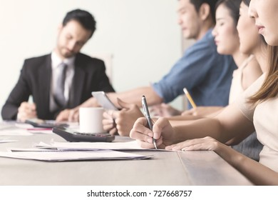 Hand of business woman who is writing notes at meeting room in office.