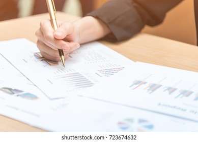 Hand of business woman woker write idea in paper with pen among chart, graph document in office.