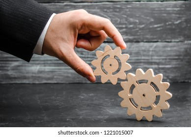 The hand of a businessman adds a gear to a large gear. The concept of business management, the search for compromise, the establishment of processes and improving business efficiency, profit growth.