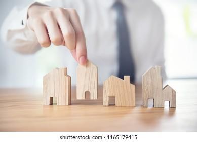 Hand of businessman choosing house model, Planning buy Real Estate.