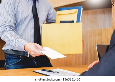 Hand of a businessman hands over a resignation letter final remuneration to executive boss on a wooden table to his boss Change of job, unemployment concept.