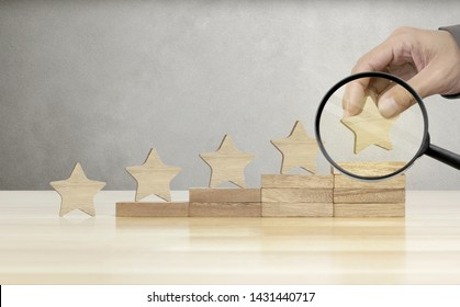 Hand of Businessman Held Magnifying Glass and putting Wooden Five Star Shape on Table, The Best Excellent Human Resources Management and Recruitment Business Hiring Concept.