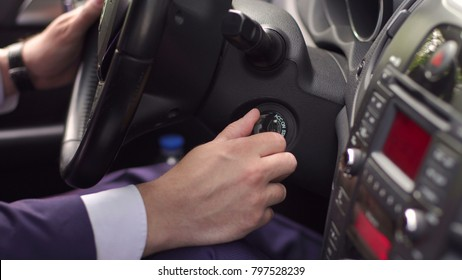Hand businessman holding car key for starting car. Businessman hand starting the car. Male driver turning ignition key in car.
