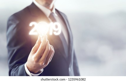 Hand of businessman holding light bulb and number 2019 year, Business idea new year concept. copy space.