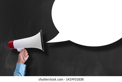 hand of businessman holding megaphone or bullhorn against blackboard with empty speech bubble
