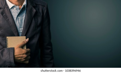 Hand of a businessman holding a notebook reminder.