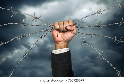 Hand of businessman holding on a barbed wire , Business heavy tasks and problems concept , Business risk concept.