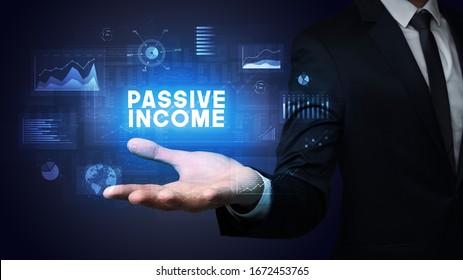 Hand of Businessman holding PASSIVE INCOME inscription, business success concept
