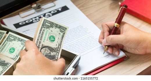 Hand of businessman holding pen to write business document and contact sheet near black coffee with warm morning light near the window.Copy space.