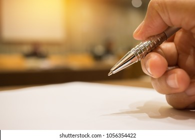 Hand Businessman holding silver pen to taking notes on white paper at conference meeting room in seminar on indoors blur people background