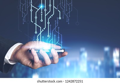 Hand of businessman holding smartphone with circuits emerging from it over night cityscape background. Toned image double exposure mock up