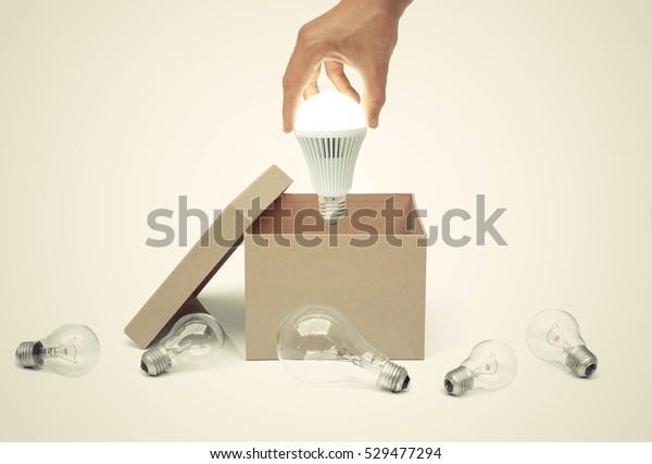 Hand eines Geschäftsmanns, der eine eingeschaltete LED-Glühlampe aus einer braunen Papierschachtel hält, umgeben von alten Glühlampen / Business mit neuer Idee und Innovationskonzept