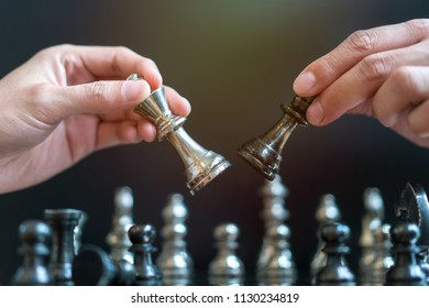 hand of businessman moving chess board game in competition success play.