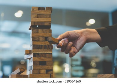 hand of businessman placing or pulling out wood block on the tower. plan and strategy in business. blur for background