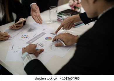 Hand of businessman point to graph. is discussing together in conference room talk about Report, Sales, Target, Marketing, Concept.