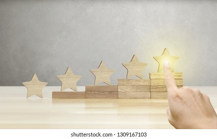 Hand of businessman pointing wooden five star shape on table, The best excellent business services rating customer experience concept.