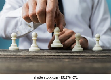 Hand of a businessman positioning white pawn chess piece in front of the others on a rustic wooden desk.