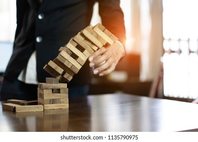 Hand of businessman pulling wood block fail on building tower at home and drape change, choice business risking dangerous project plan failure construction,Selective block wooden