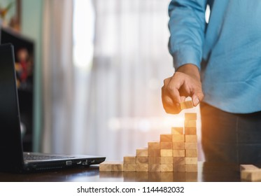 Hand of businessman pulling wooden block before fail on building tower at home and drape change, choice business risking dangerous project plan failure construction