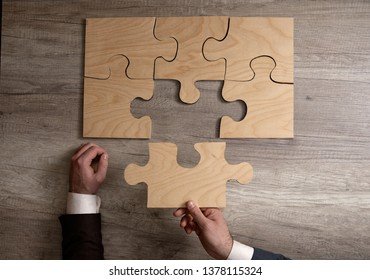 Hand of businessman put the last piece of jigsaw puzzle to complete the mission, concept must important part, finishing complicated project, solution, triumph