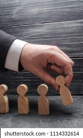 The hand of a businessman puts a wooden figure of a man in a row to other employees. The concept of business management, personnel policy, human resources. Specialists, career growth.