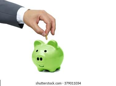 hand of a businessman putting a golden coin into a big  green piggy bank - green saving concept