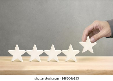 Hand of businessman putting increase white five star shape on table, The best excellent business services rating customer experience concept.