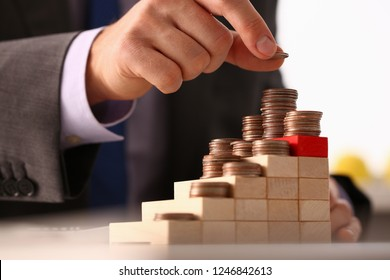 Hand businessman putting pin money financial pyramid tower. Future needs loan education or mortgage credit spend vacation of dream effective buying financial risk and safety concept