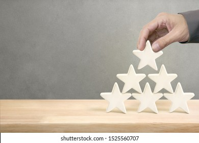 Hand of businessman putting white five star shape on top of pyramid, The best excellent business services rating customer experience concept.
