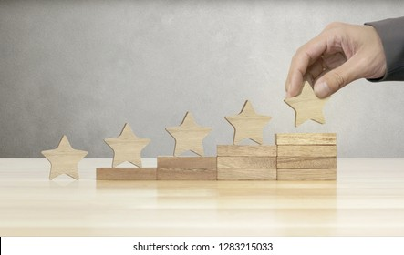 Hand of businessman putting wooden five star shape on table, The best excellent business services rating customer experience concept.