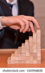 The hand of a businessman reached the goal of the wooden blocks