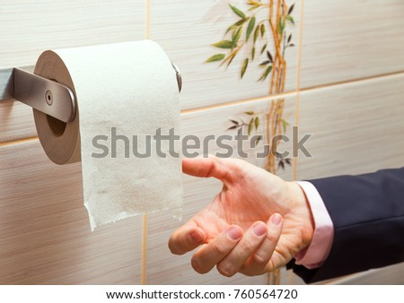 Hand of a businessman reaching for toilet paper