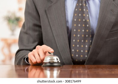 hand of businessman ringing hotel bell in reception desk close up selective focus