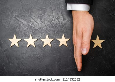 The hand of the businessman separates the fifth star from the other four. The loss of the fifth star, the fall in rating and recognition. The critic takes the fifth star from the hotel, restaurant.