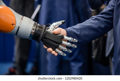 Hand of a businessman shaking hands with a droid robot.. The concept of human interaction with artificial intelligence.