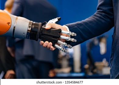 Hand of a businessman shaking hands with a robot. The concept of human interaction with artificial intelligence.