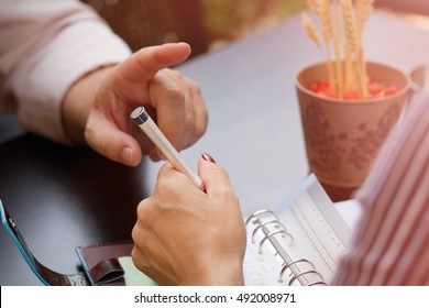 Hand of businessman show objection gesture on strategy discussion.Conversation at business lunch meeting in cafe outdoors.Female model writing in notebook.Brilliant idea concept