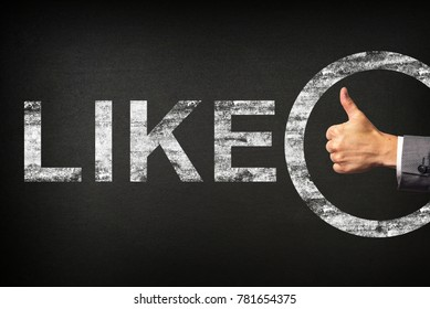 Hand of a businessman showing thumbs up for the phrase LIKE written on a blackboard