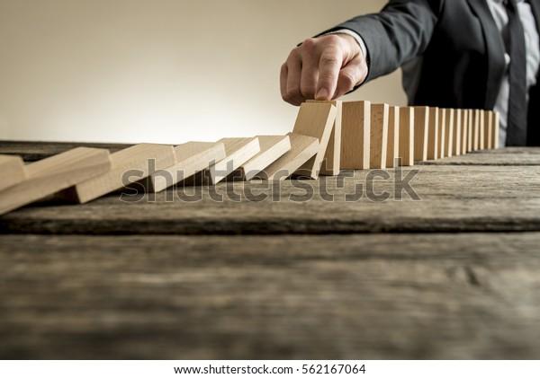 Mano de hombre de negocios que deja de caer piezas de dominó. Incluye una copia sobre una mesa de madera.