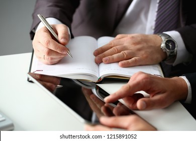 Hand of businessman in suit filling and signing with silver pen partnership agreement form clipped to pad closeup. Management training course some important document, team leader ambition concept