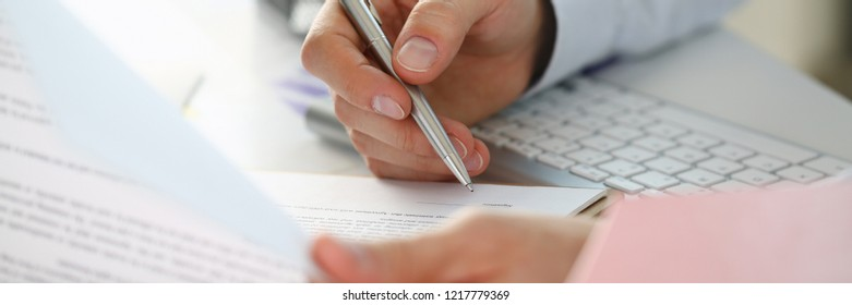 Hand of businessman in suit filling and signing with silver pen partnership agreement form clipped to pad closeup. Management training course some important document team leader ambition concept