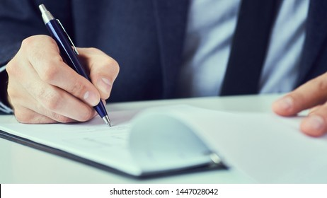 Hand of businessman in suit filling and signing with blue pen partnership agreement form clipped to pad closeup.