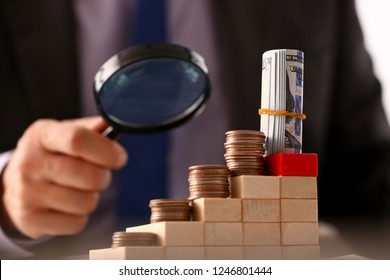 Hand businessman in suit hold lens background looking through money towers closeup search business concept