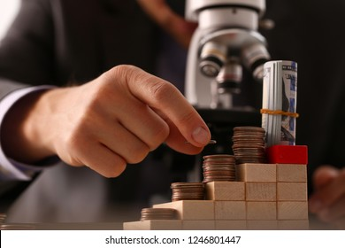Hand businessman in suit hold quarter in background looking through microscope closeup search business concept