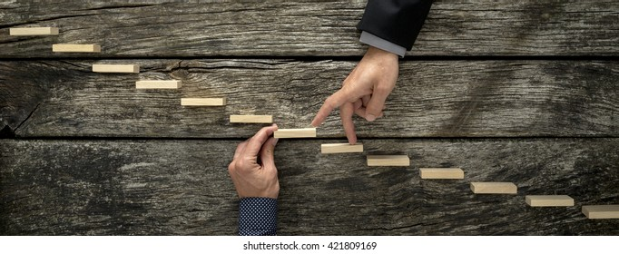 Hand of a businessman supporting a wooden step for his colleague to walk his fingers up towards success, conceptual of business teamwork and collaboration.